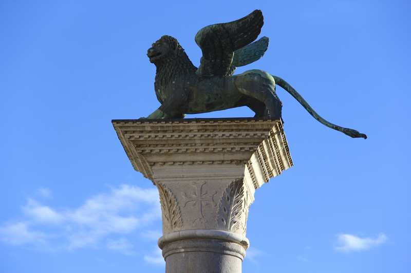 The Lion of San Marco perches atop a tall pillar outside of the piazza